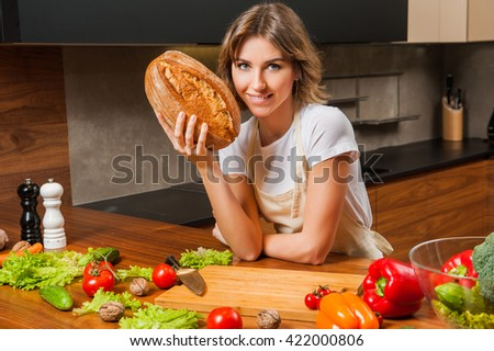 pretty young housewife holding bread in her hands