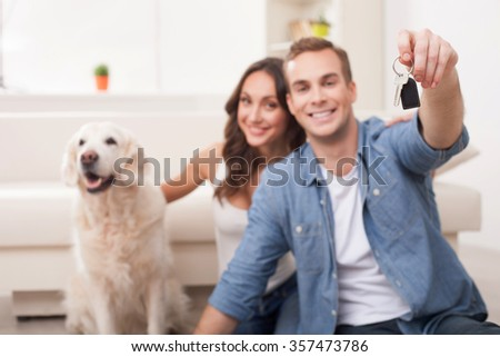 Pretty young husband and wife are preparing for move in new house. They are sitting on flooring and smiling. The man is holding a key. The woman is stroking a dog - stock photo