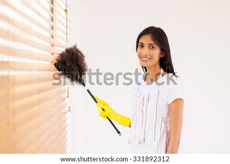pretty young indian woman cleaning window blinds with feather duster - stock photo