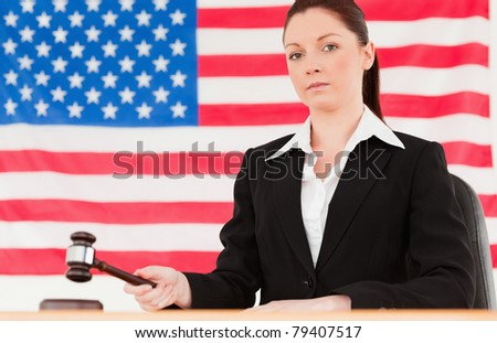 Pretty young judge knocking a gavel with an American flag in the background - stock photo