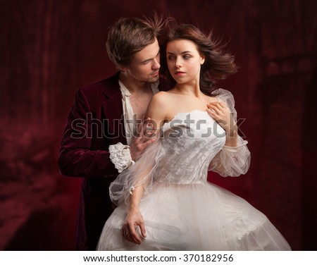 pretty young lady in old time and man in green in medieval dress over red