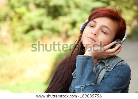 pretty young lady listening to music in the park - stock photo