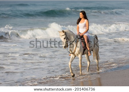 pretty young lady riding a horse on the beach in early morning - stock photo
