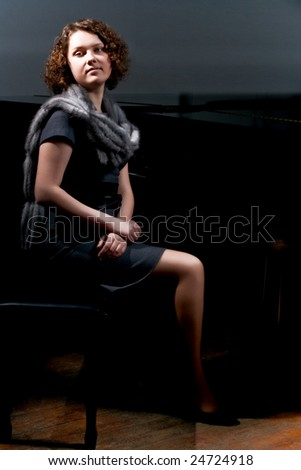 pretty young lady sitting near black piano in grey dress with fur scarf around neck isolated - stock photo