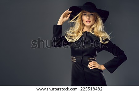 Pretty young lady wearing black hat, in a fashion pose  - stock photo