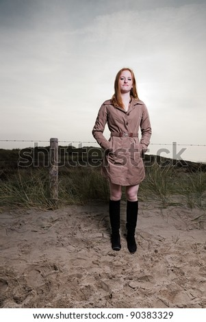 Pretty young lady with red hair and blue eyes outdoor standing in dunes landscape at the beach in autumn.