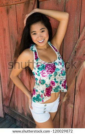 Pretty young Laotian woman in a flower print blouse and white shorts - stock photo