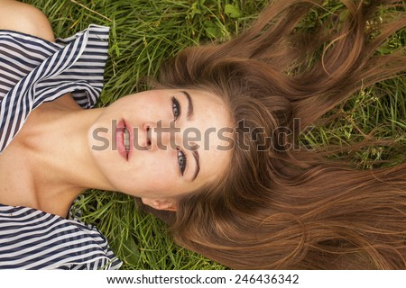Pretty young long-haired girl lying on the green grass, close-up. - stock photo