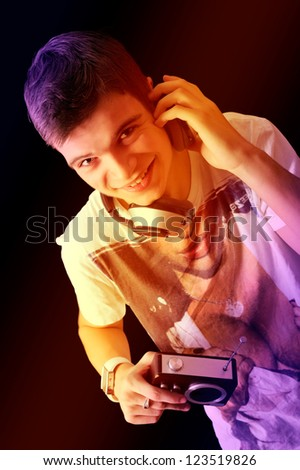 Pretty young man in phones with an old radio - stock photo