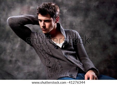 Pretty young man posing on dark background - stock photo