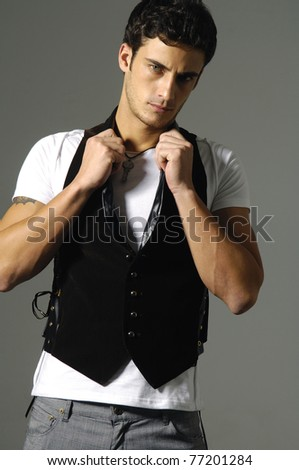 Pretty young man posing on gray background - stock photo