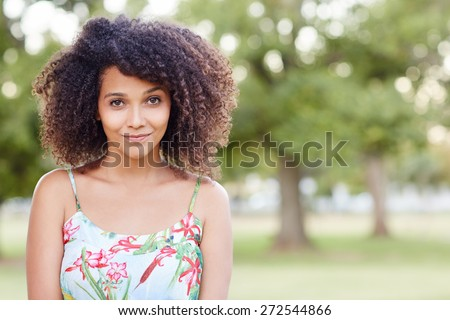 Pretty young mixed race woman smiling sweetly at the camera in a green park  - stock photo