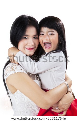 Pretty young mother and her daughter smiling at camera in studio - stock photo