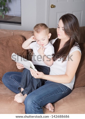 Pretty young mother reading with her son on a mobile wireless tablet computer device at home in the living room. - stock photo