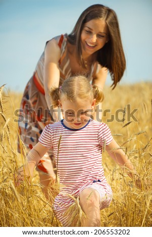 Pretty young mother with cute little daughter at wheat field - stock photo