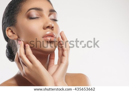 Pretty young mulatto woman enjoying skincare treatment - stock photo