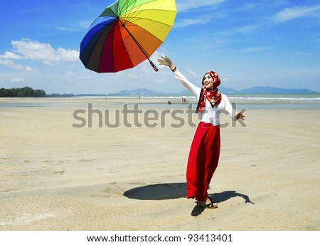 Pretty young Muslim lady in happy while released a umbrella. - stock photo