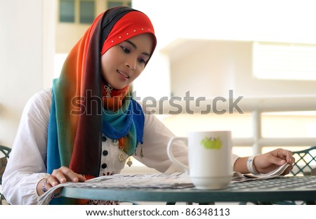 pretty young muslim reading the newspaper outside balcony - stock photo