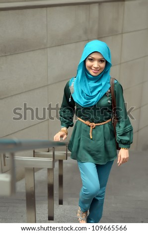 Pretty young muslim woman walk to shopping mall - stock photo