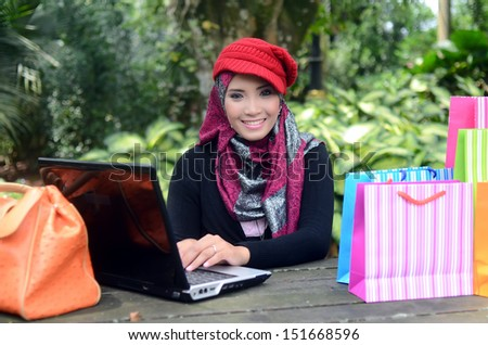 Pretty young muslim woman with notebook and shopping bag - stock photo