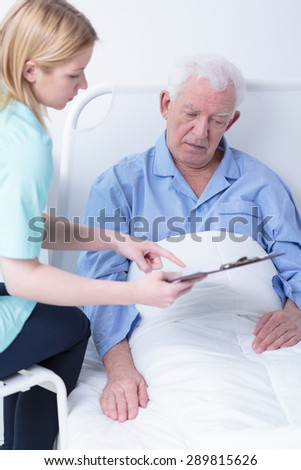 Pretty young nurse showing elderly concerned patient rest results