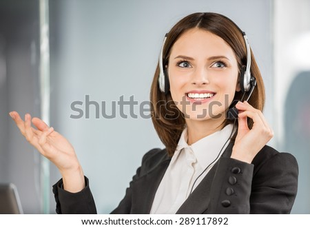 Pretty young phone operator with headset working at call center.