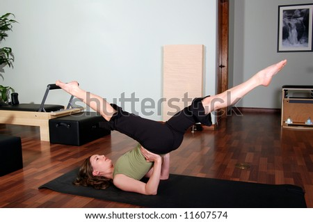 Pretty Young Pilates Instructor Performing Floor Excercise
