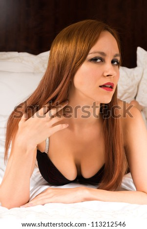 Pretty young redhead in red and black lingerie - stock photo