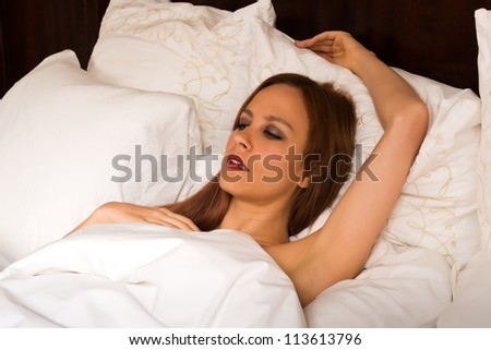 Pretty young redhead lying nude in bed - stock photo