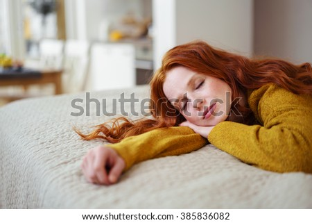 Pretty young redhead woman taking a nap as she spends a relaxing day at home lying on her stomach on her bed - stock photo
