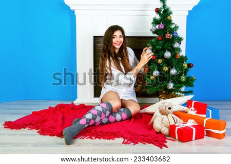 Pretty young sensual girl with natural make up and amazing long hairs decorate Christmas tree at home. Cozy cute holiday atmosphere. - stock photo