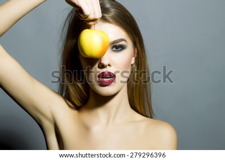 Pretty young sexy girl with bright make up looking forward holding fresh yellow apple covering eye standing on gray background copyspace, horizontal picture - stock photo