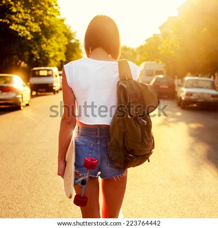 Pretty young sexy hot woman in short jeans shorts and hot body walking outdoor on the road in summer evening with backpack and longboard  - stock photo