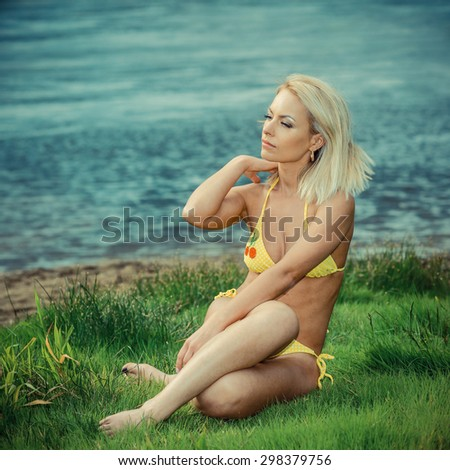 Pretty young sexy tanned woman in bikini posing outdoor in summer  - stock photo