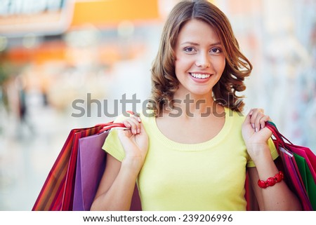 Pretty young shopaholic with paper-bags