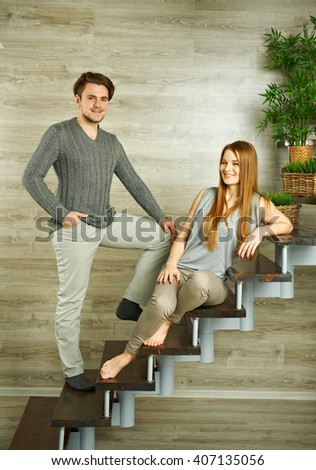 Pretty young smiling couple on stairs - stock photo