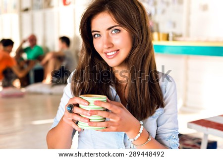 Pretty young smiling dir drinking cappuccino  in cute cafe, waiting for her fiends liking on camera, fresh face, make up, brunette long hairstyle, sunny colors. - stock photo