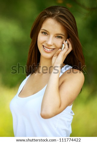 Pretty young smiling woman talking on cell phone, against green of summer park. - stock photo
