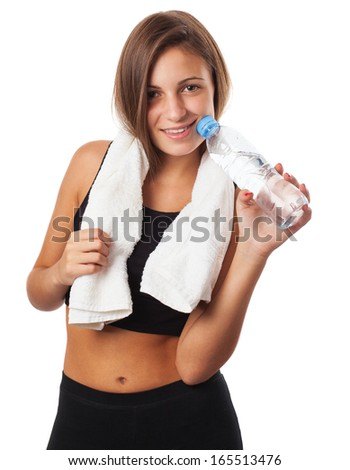 pretty young sporty woman holding a water glass and a towel on white background
