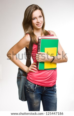 Pretty young student girl with colorful exercise books.