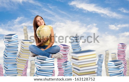 pretty young student holding a earth globe sitting on a big books pile - stock photo