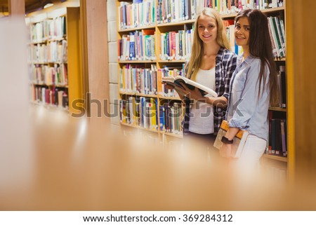 Pretty young students working together with book in library - stock photo
