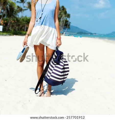 Pretty young tanned woman posing on the beach ready to summer vacation trip  - stock photo