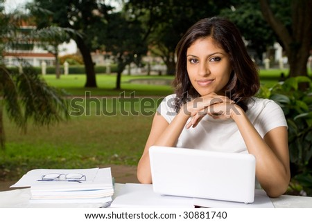 pretty young university student outdoors with laptop - stock photo