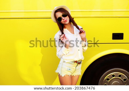 Pretty young vintage dressed hipster girl posing in summer on yellow wall background  - stock photo