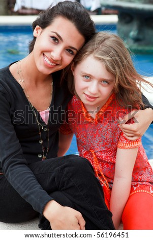 Pretty young woman and girl in a lifestyle pose by a park fountain,family