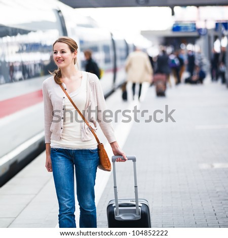 Pretty young woman at a train station (color toned image) - stock photo