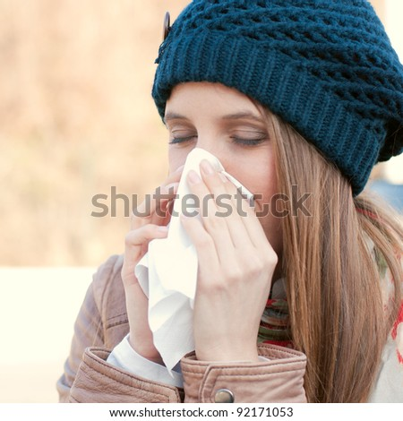 Pretty young woman blowing her nose with a tissue outdoor in winter - stock photo