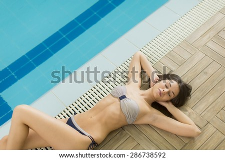 Pretty young woman by the pool - stock photo