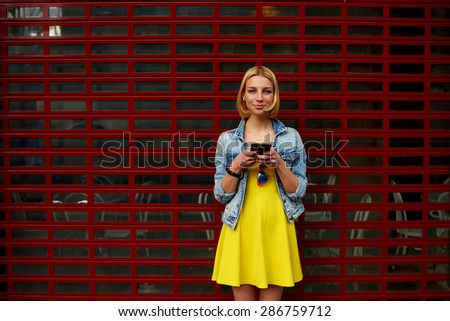 Pretty young woman chatting on smart phone against blank copy space bright background for your content or text message,smiling female hipster in the dress using mobile phone for connect to wireless - stock photo